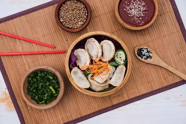 Dumpling avec salade au steamer en bambou entouré de ciboulette; graines de coriandre et baguettes sur napperon Photo gratuit