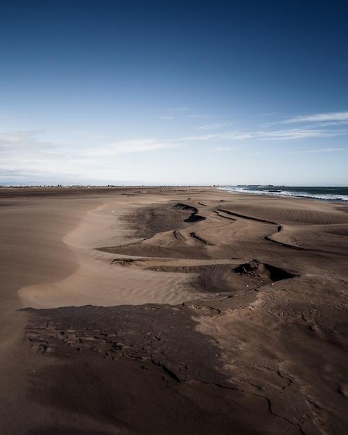 Dunes De Sable Brun à La Plage Sous Le Ciel Bleu Photo gratuit