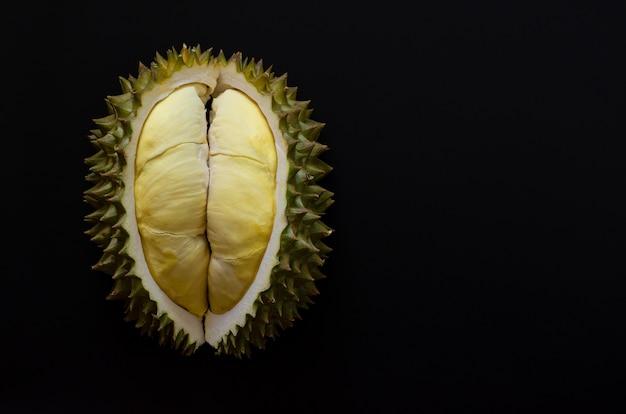 Durian frais coupé qui est le roi des fruits de thaïlande isolé sur fond noir avec un espace pour le texte. Photo Premium