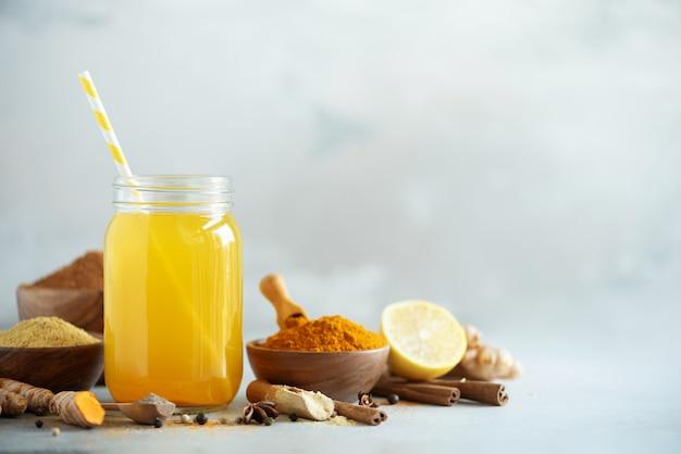 Eau citronnée au gingembre, curcuma, poivre noir. concept de boisson chaude végétalien. ingrédients pour boisson au curcuma orange sur fond de béton gris Photo Premium