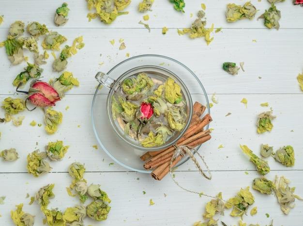 L'eau Dans Une Tasse Avec Des Herbes Séchées, Des Bâtons De Cannelle Vue De Dessus Sur Une Table En Bois Photo gratuit