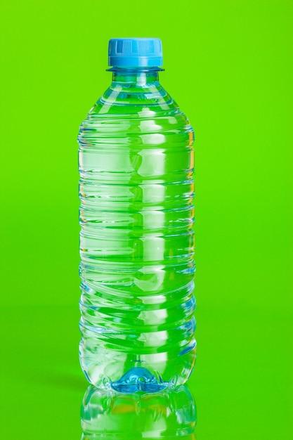 Eau limpide dans une bouteille sur fond vert Photo Premium