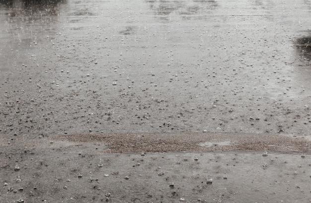 L'eau de pluie route tombe de fond avec la réflexion de ciel bleu et des cercles sur l'asphalte sombre. prévoir. Photo Premium