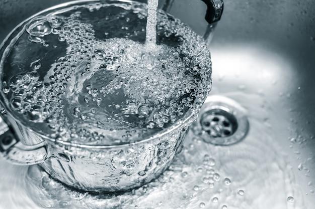 Eau propre dans l'évier de la cuisine, eau de rinçage dans les déchets de la casserole du ménage Photo Premium