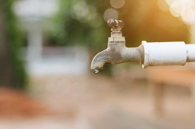 Eau qui coule du vieux robinet rouillé avec flou vert le fond du parc en plein air Photo Premium