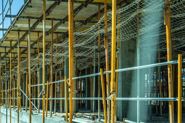 Échafaudage soutenant le coffrage de piliers en béton de certains bâtiments en construction. Photo Premium