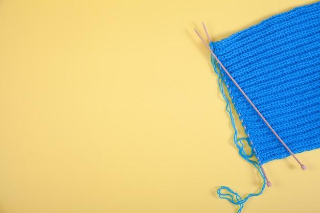 L'écharpe Bleue Tricotée Se Trouve Sur Un Fond Jaune. Concept Fait à La Main. Copiez L'espace. Photo Premium