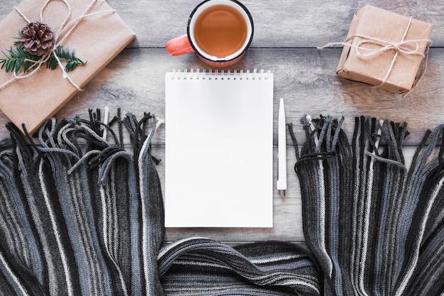 Echarpe et cahier près du thé et des cadeaux Photo gratuit