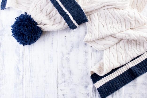 Écharpe D'hiver Tricotée Et Un Bonnet Blanc Avec Une Bande Bleue Sur Un Fond En Bois Blanc. Espace Copie Pour Le Texte Carte De Voeux De Bonne Année Thème D'hiver Photo Premium