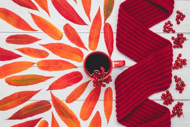 Écharpe Tricotée Chaude Et Tasse De Thé Avec Des Feuilles Rouges Sur Planche De Bois, Composition D'automne. Photo Premium