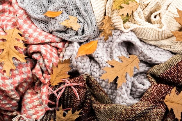 Écharpes chaudes et fond de feuilles Photo gratuit