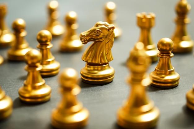 Échecs en or sur fond noir, se concentrer sur le chevalier Photo Premium