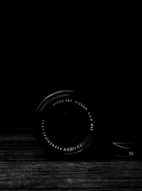 Échelle De Gris Verticale Prise De Vue D'un Objectif D'appareil Photo Sur Une Surface En Bois Photo gratuit