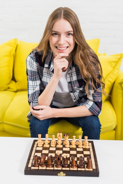 Echiquier en bois sur une table blanche devant une jeune femme souriante assise sur un canapé Photo gratuit