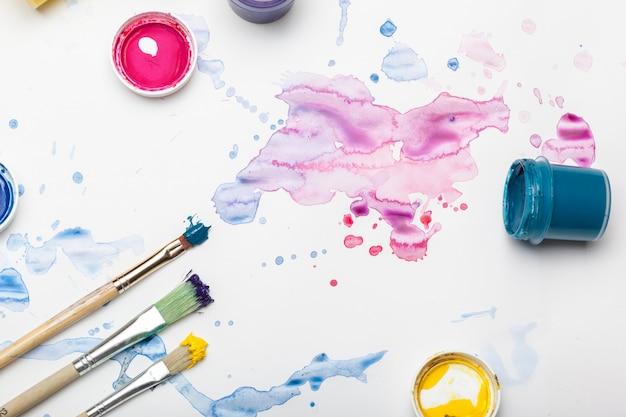Des éclaboussures de peinture à l'aquarelle et des fournitures de peinture se bouchent Photo Premium
