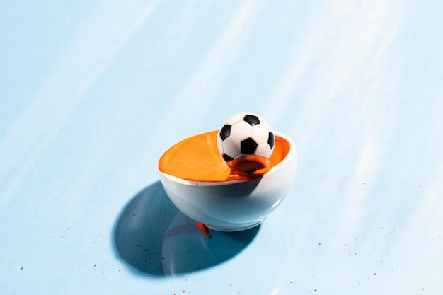 Éclaboussures de peinture orange avec ballon de foot Photo gratuit