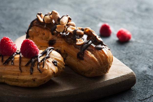 Eclairs aux cacahuètes, glaçage au chocolat et framboises Photo Premium