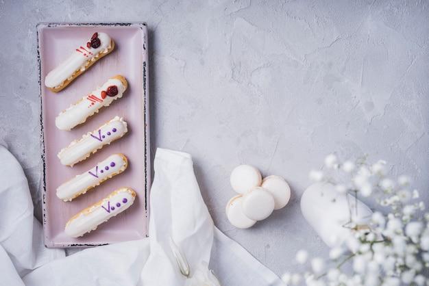 Eclairs à la crème avec des macarons et un vase à fleurs de souffle de bébé Photo gratuit