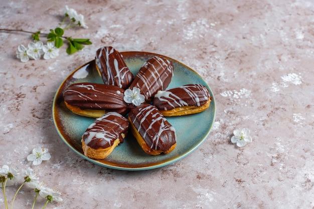 Eclairs Ou Profiteroles Au Chocolat Noir Et Chocolat Blanc Avec De La Crème Anglaise à L'intérieur, Dessert Français Traditionnel.vue D'en Haut. Photo gratuit