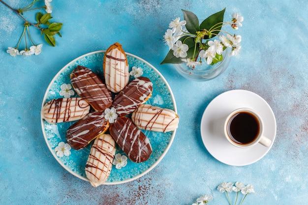 Eclairs Ou Profiteroles Au Chocolat Noir Et Chocolat Blanc Avec Crème Pâtissière à L'intérieur, Dessert Traditionnel Français. Vue De Dessus. Photo gratuit