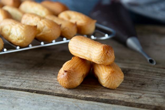 Eclairs ou profiteroles - dessert français. cuisson des biscuits maison. Photo Premium
