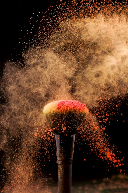 Éclat de poudre et pinceau de maquillage sur fond sombre Photo gratuit
