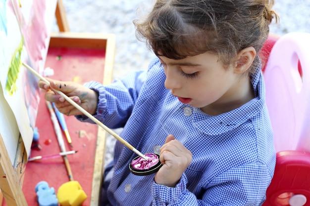 École artiste petite fille peinture aquarelles portrait Photo Premium