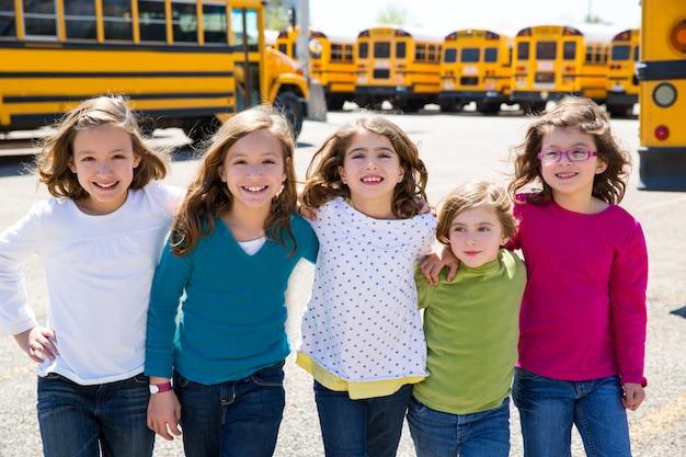École filles amis dans une rangée à pied de bus scolaire Photo Premium