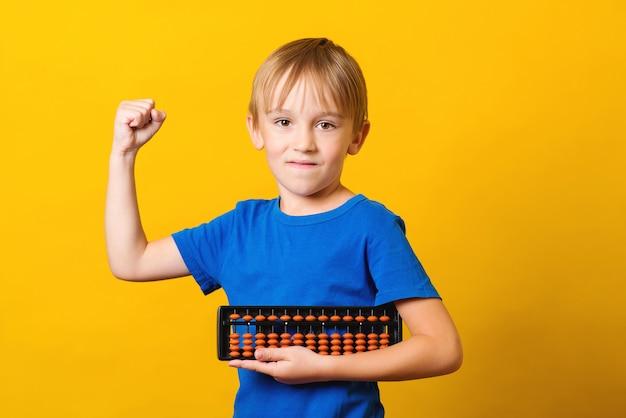 Écolier Avec Abaque Sur Fond Jaune. étude D'enfant à L'école D'arithmétique Mentale. Photo Premium
