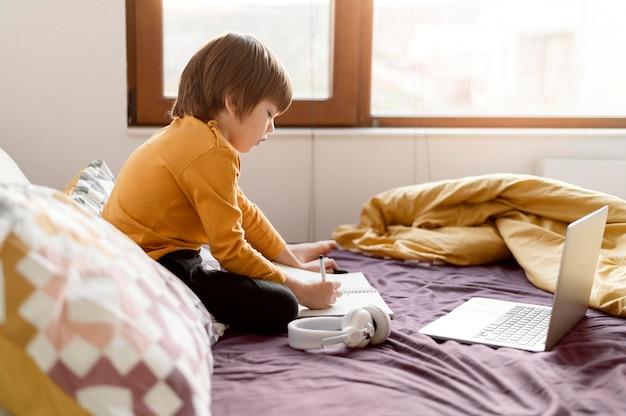 Écolier Assis Dans Son Lit Sur Le Côté Photo gratuit