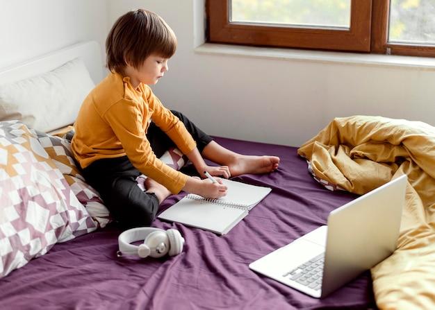 Écolier Assis Dans Son Lit école Virtuelle Photo gratuit