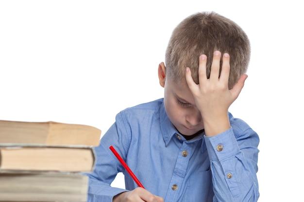 Un écolier fait ses devoirs à la table. tristesse et fatigue d'étudier. isolé sur blanc. Photo Premium