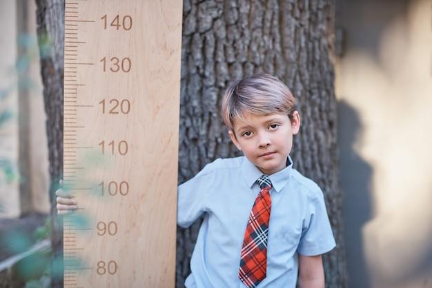 Écolier avec grosse règle debout sur fond en bois. adieu bell. jour de connaissance. Photo Premium