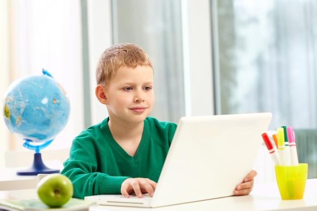 Écolier Avec Un Ordinateur Portable Sur Son Bureau Photo gratuit