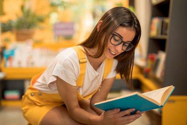 Écolière adolescente accroupie avec livre Photo gratuit