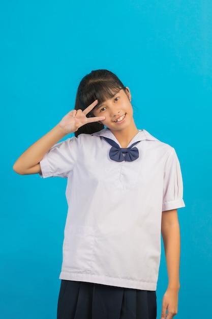 Écolière Asiatique Mignonne Montrant Deux Doigts Sur Un Bleu. Photo gratuit