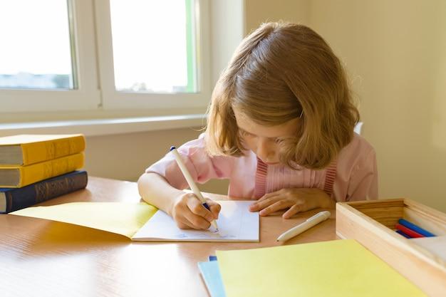 Écolière assis à table avec des livres et écrire dans un cahier Photo Premium