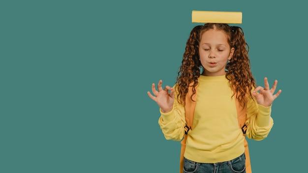 Écolière Avec Chemise Jaune Tenant Un Livre Sur L'espace De Copie De Tête Photo gratuit
