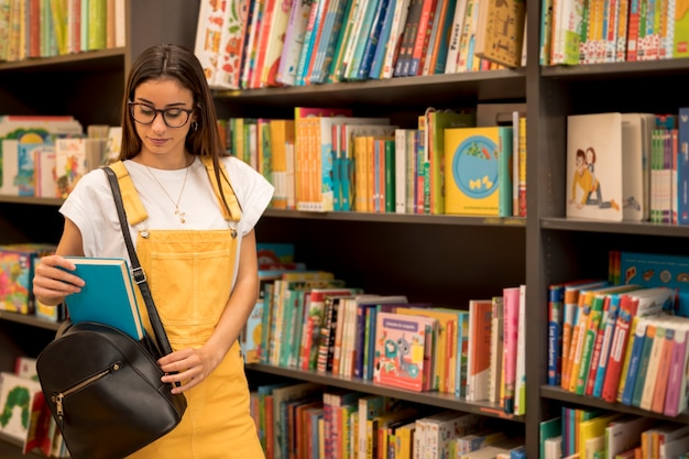 Écolière debout tenant un livre dans un sac à dos Photo gratuit