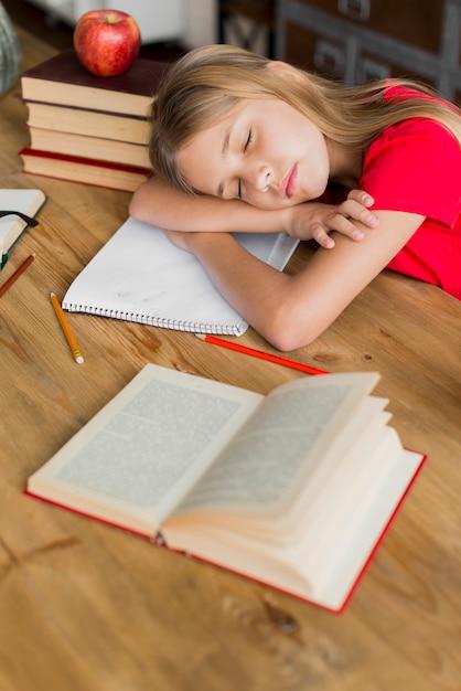 Écolière dormir au milieu de manuels scolaires Photo gratuit