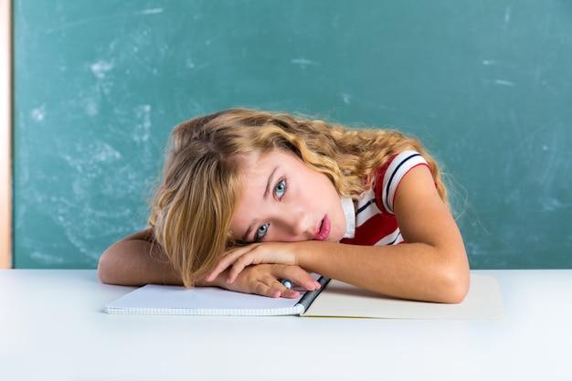Écolière étudiant d'expression triste ennuyeux sur le bureau Photo Premium