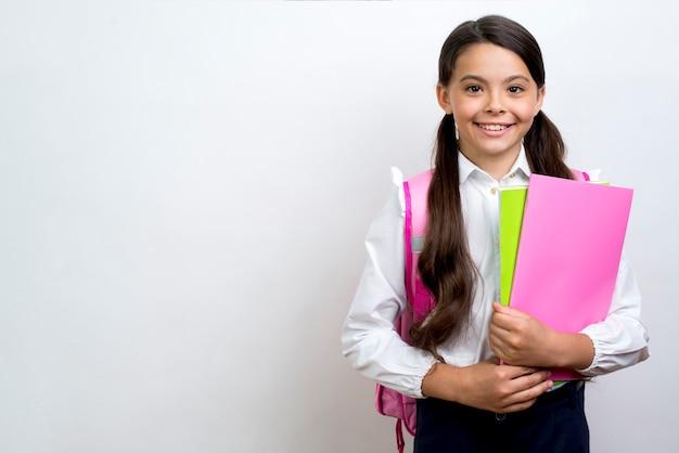 Écolière Hispanique Excité Portant Des Cahiers Photo gratuit
