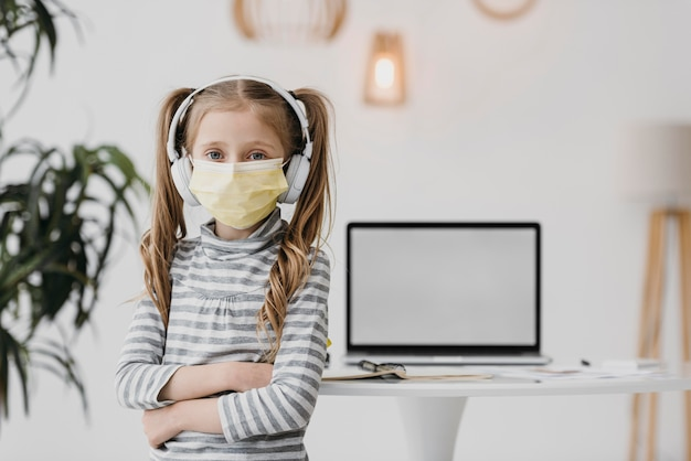 Écolière Portant Un Masque Médical à L'intérieur Photo gratuit