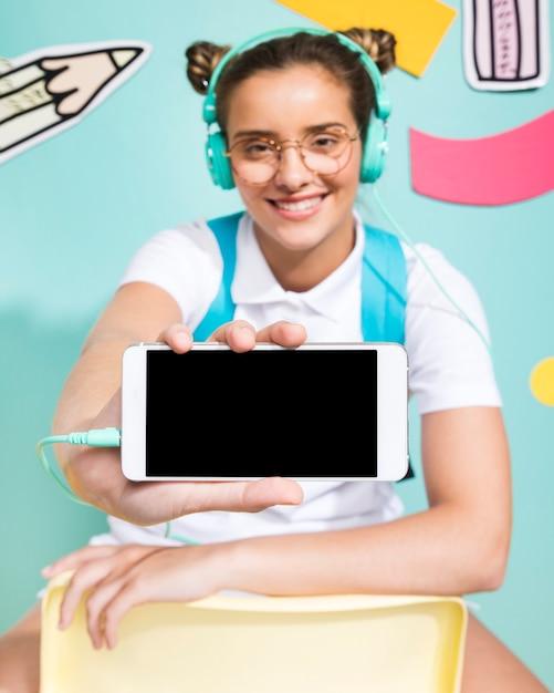 Écolière présentant un modèle de smartphone Photo gratuit