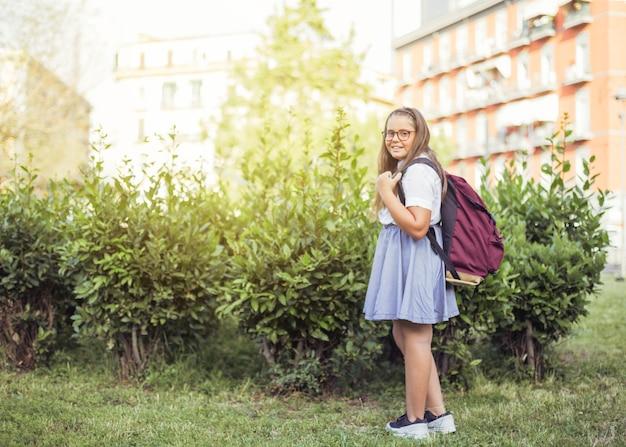Écolière avec sac à dos debout devant des buissons en souriant Photo gratuit