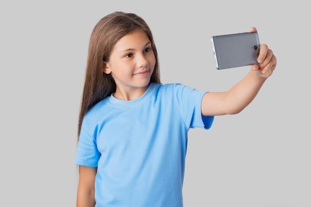 Écolière Souriante En T-shirt Bleu Prenant Selfie Avec Grand Smartphone Moderne Gris Photo Premium