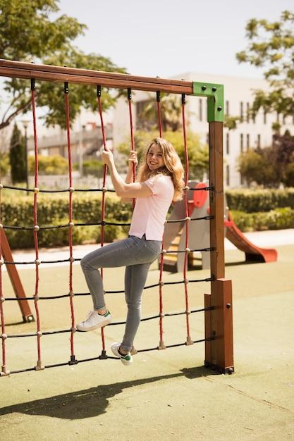 Écolière teen ludique sur filet d'escalade sur le terrain de jeu Photo gratuit