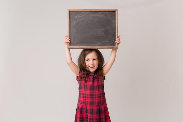 Écolière tenant une commission scolaire Photo Premium