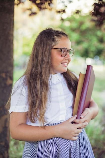 Écolière en uniforme debout dans le jardin avec des livres Photo gratuit