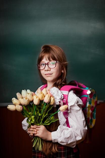 Écolière, uniforme scolaire, à, fleurs, main, tulipes, dos, dos, école Photo Premium